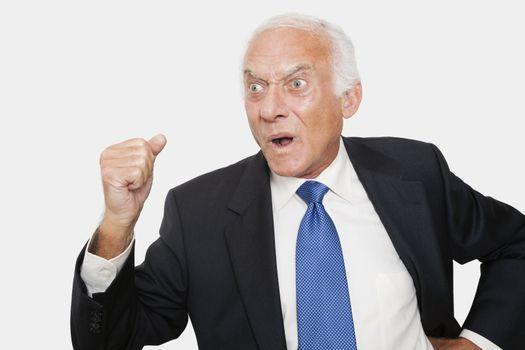 Aggressive elderly businessman against white background