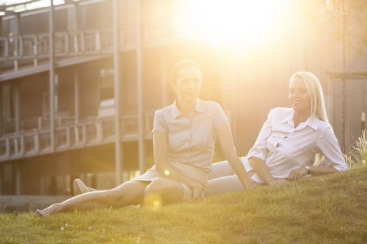 Young businesswomen relaxing on office lawn