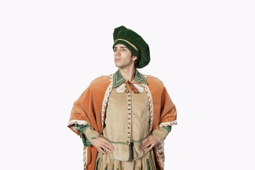 Thoughtful young man in old-fashioned costume with hands on hips against gray background