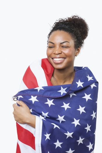 Cheerful young woman wrapped in American flag over white background