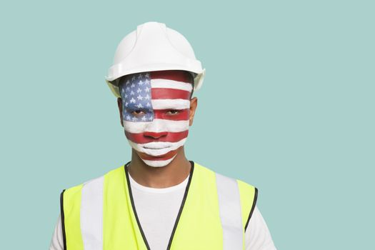 Portrait of young architect with American flag painted on face against colored background