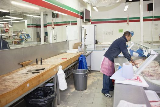 Full-length of male employee organizing meat in supermarket