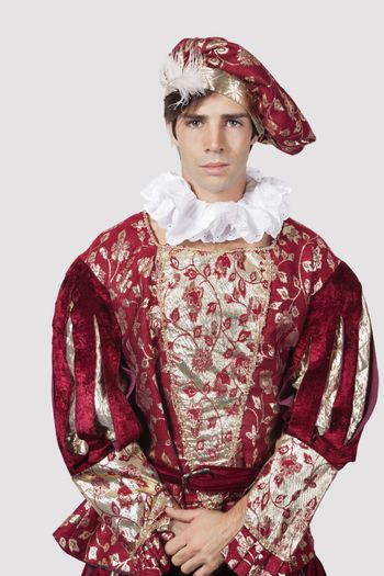 Portrait of young man in old-fashioned costume against gray background