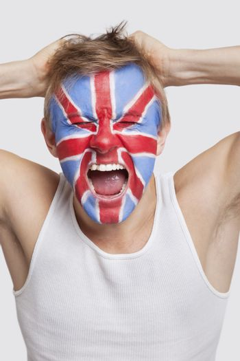 Frustrated young Caucasian man with British flag painted on face screaming against white background