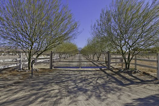 Front gate of ranch with dirt road.