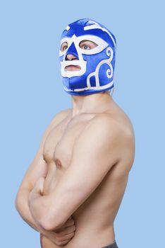 Portrait of shirtless man in wrestling mask gesturing over gray background
