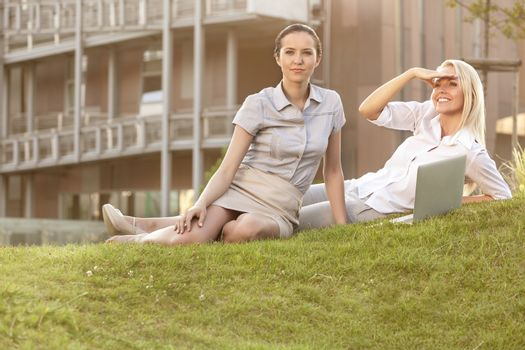 Young businesswomen with laptop on office lawn