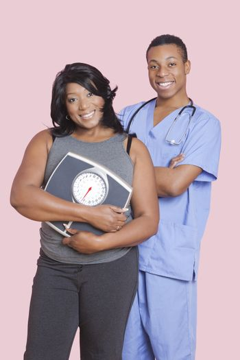 Overweight mixed race woman holding scales over pink background