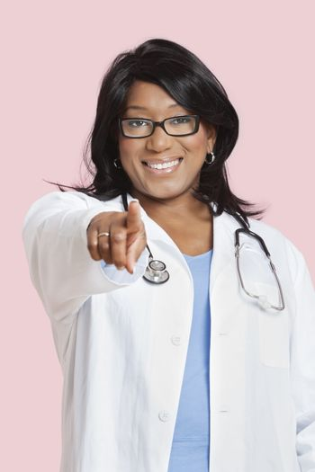 Portrait of mixed race female surgeon pointing at you over pink background