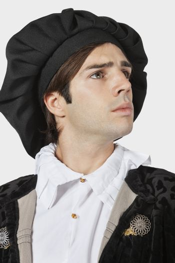 Young man in old-fashioned costume against gray background