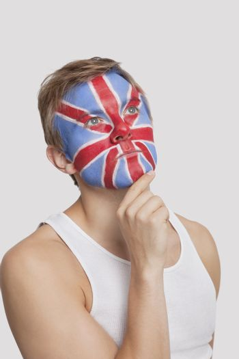 Pensive young Caucasian man with British flag painted on face against white background