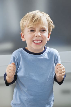 Angry Caucasian boy in sleepwear clenching his teeth