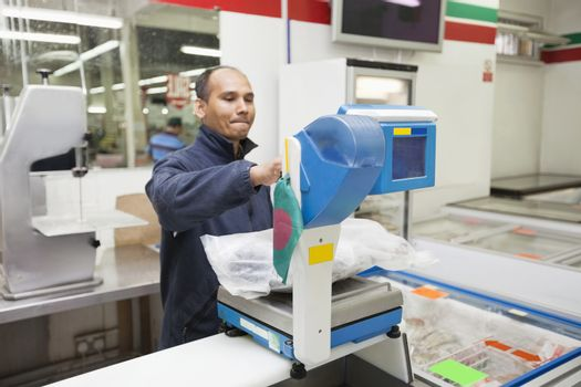 Employee weighing product in supermarket