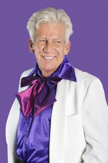 Portrait of happy senior man wearing old-fashioned suit against purple background