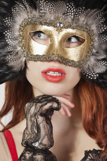 Young woman with feathered eye mask looking away against gray background