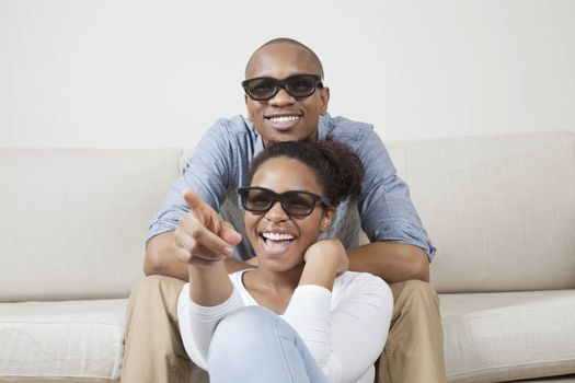 Portrait of young African American couple wearing 3D glasses and watching TV