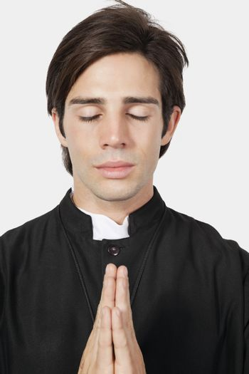 Young man in priest costume praying against gray background