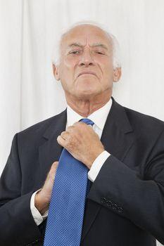 Portrait of confident elderly businessman adjusting his necktie