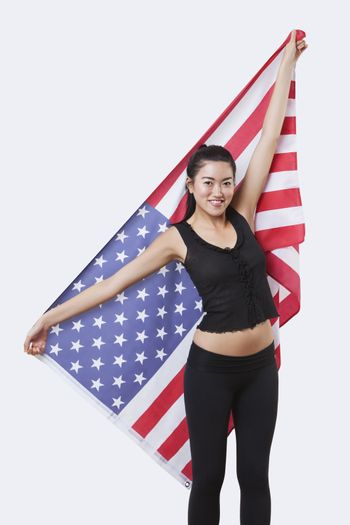 Portrait of smiling young woman holding American flag over white background