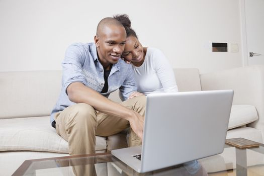 Happy African American young couple using laptop at home