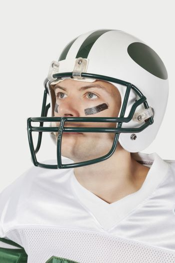 Portrait of confident young man wearing football uniform against gray background
