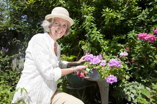 Portrait of happy senior woman with shovel gardening in backyard