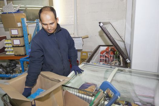 Male worker loading products in refrigerator at grocery store