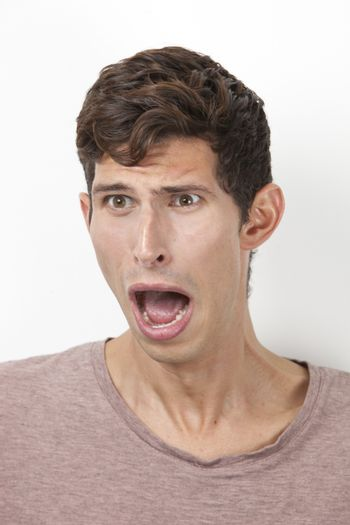 Frightened young man screaming against white background