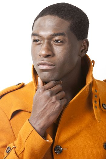 Thoughtful young man in orange trench coat looking away against white background