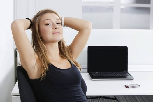 Portrait of young businesswoman with hands behind head sitting in front of desk in office