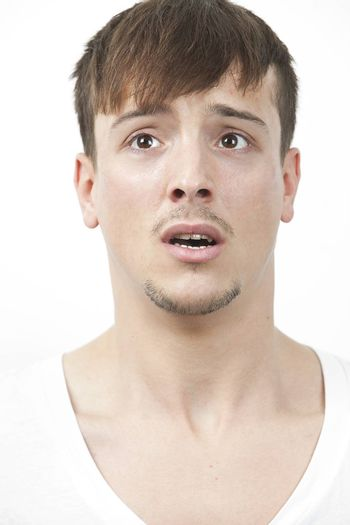 Fearful young man looking away over white background
