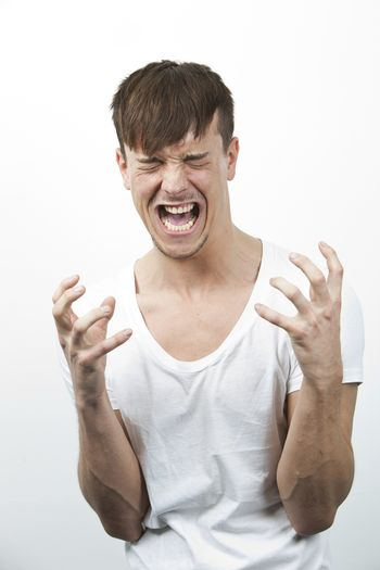 Aggressive young man screaming against white background