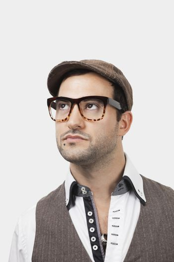 Thoughtful young Caucasian man in flat cap against white background