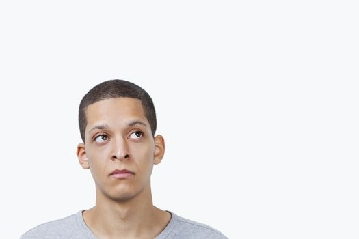 Thoughtful young mixed race man looking sideways against white background