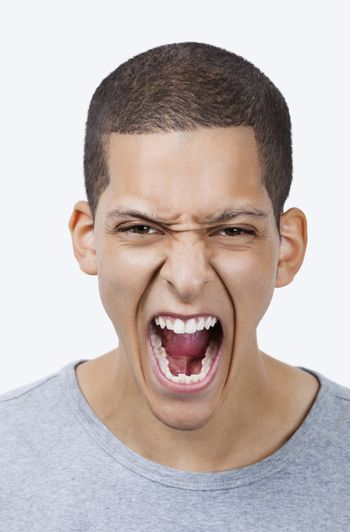 Portrait of aggressive young mixed race man screaming against white background
