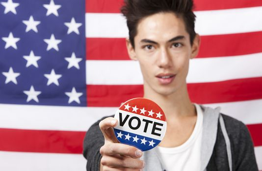 Portrait of young man displaying vote badge against American flag