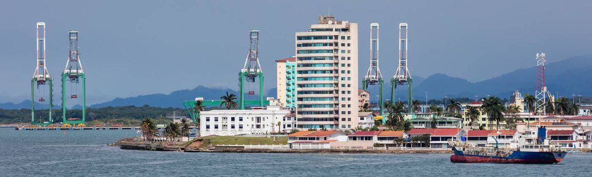 Panoramic view of a port in Panama next to Panama canal. Massive shipyard cranes and buildings in the background, fuel tanker in the foreground.