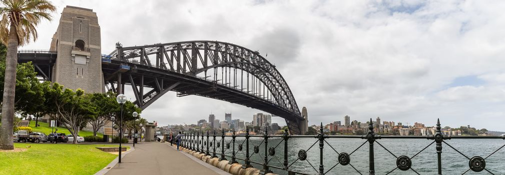Sydney Harbor, Australia - October 23, 2018: View of Sydney harbor bridge. Cars parked next to it and tourists walking underneath it.