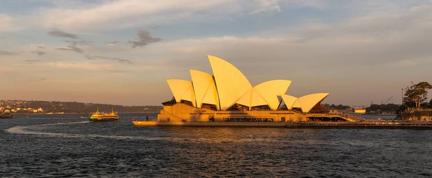 Sydney Harbor, Australia - November 1, 2018: Sydney Opera House at sunset. Boat circling the house in the bay. Beautiful orange-and-yellow colors. Cloudy sky in the background.