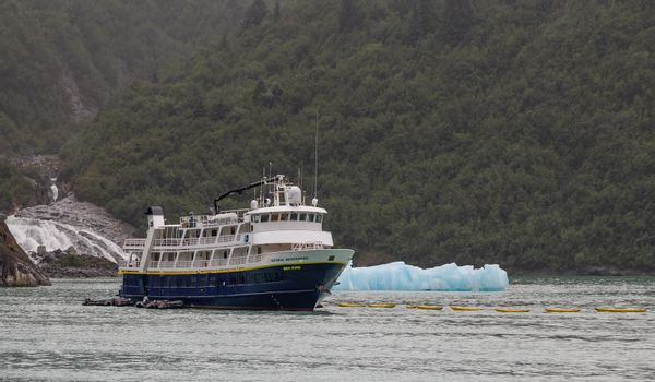 Tracy Arm Fjord, Alaska, US - August 23, 2018: National Geographic's Sea Bird vessel drifting with a mountain, a waterfall, and an iceberg behind it in Tracy Arm Fjord in Alaska, USA