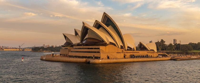 Sydney Harbor, Australia - November 1, 2018: Close view of Sydney Opera House at sunset. Beautiful orange-and-yellow colors. Cloudy sky in the background.