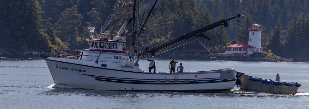 Sitka, Alaska, USA - September 10, 2018: Fishing boat Lisa Jean sailing in marina. Lighthouse and forest in soft focus in the background. Sitka, Alaska, USA