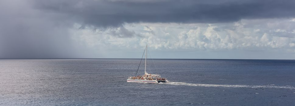 Cozumel, Mexico - December 17, 2019: Catamaran Fury sailing by the island of Cozumel in Mexico. Catamaran full of tourists. Stormy weather in the background