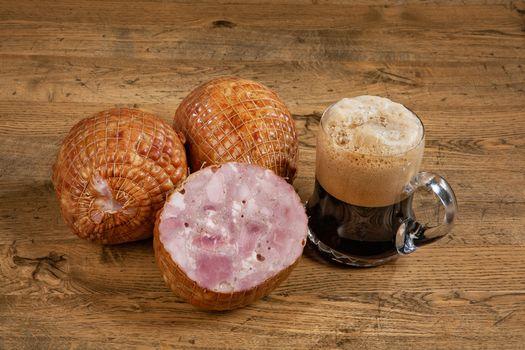Ham sausage and mug of dark beer on a wooden desk