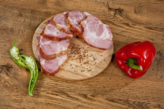 Ham sausage and pepper on a wooden desk