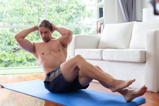 Close up of young man having exercise on mat in living room at home