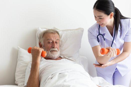 Senior retirement man doing dumbbell fitness training with  physiotherapist