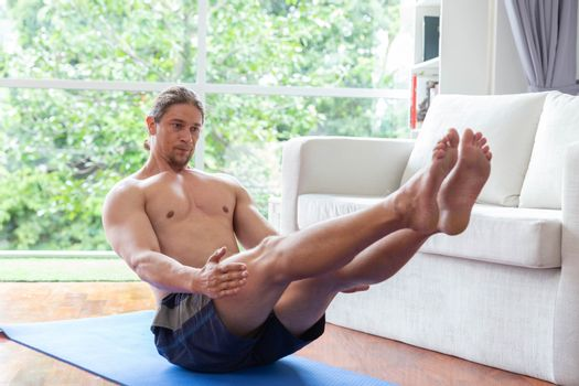 Close up of young man doing v-up exercise on mat in living room at home