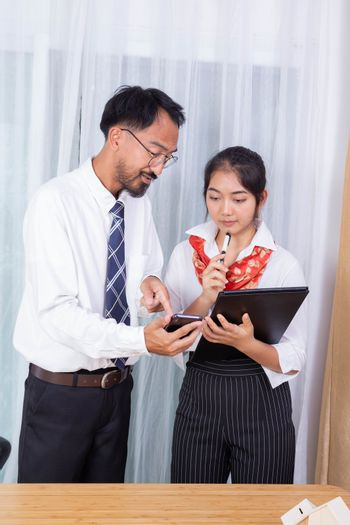 two asian male and female as business partner working with mobile phone