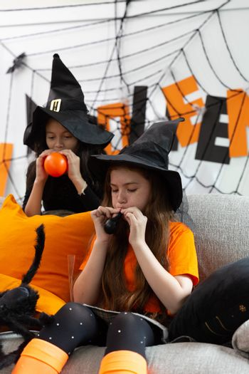 Happy Halloween by a group of children, a sister in carnival costume prepare the colorful balloon in decorated house